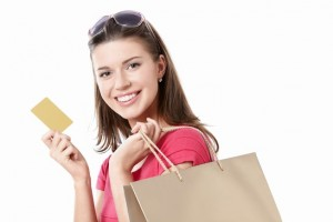 Young girl with a credit card and shopping bags isolated